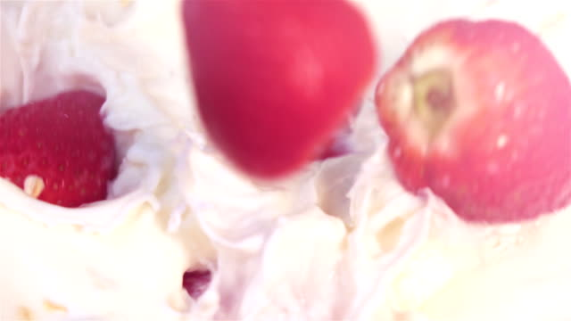 Video of strawberries falling into milk with oatmeal-real slow motion