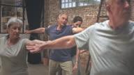 Video der Lehrer, die Gruppe der Senioren Gymnastik im Yoga-Kurs hilft