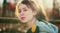 Video portrait of 16-years-old pretty girl who working outdoor, on the backyard, at autumn.