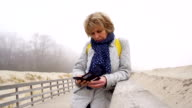 Video portrait of the 50-years-old attractive senior woman talking via cellphone on the winter's beach