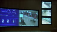 A video screen shows multiple views from security cameras.