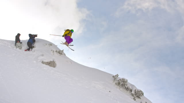 SLO MO Video shooting female skier jumping in powder snow