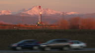 HD video vehicles drive by oil fracking drill rig and Rocky Mountains Colorado