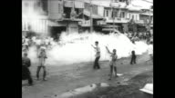 Vietnamese army troops drive past in truck in Da Nang / troops patrol streets on foot / tank rolls down street / family standing at entrance to their...