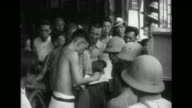 Vietnamese civilians interact with Imperial Japanese Army soldiers as city life continues under Japanese control and transportation and commerce...