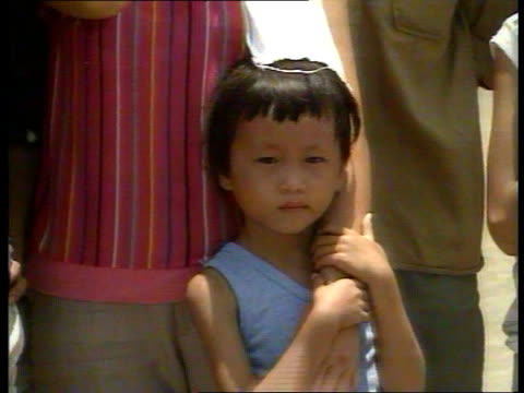 Vietnamese refugees ITN LIB EXT HONG KONG Refugee Camp MS SIDE Sir Geoffrey Howe MP along thru camp accompanied by officials followed by refugees CMS...