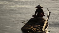 Vietnamese Woman in Conical Hat Rows Boat Filled with Fishing Baskets