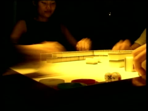 View across Mah Jong table as game being played by 4 people.