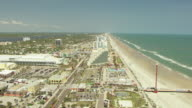 WS AERIAL View along beach and crossing over condos to Halifax River at Daytona Beach in Volusia County / Daytona Beach, Florida, United States