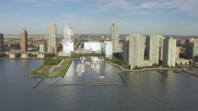 WS AERIAL PAN View along shore of Hudson river with sun reflecting off buildings / Jersey City, New Jersey, United States