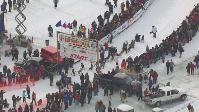 WS AERIAL ZI View approach to race start with dog sled team at start line and crowd / Willow, Alaska, United States