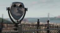 View binoculars overlooking a park, George Washington Bridge behind in the distance