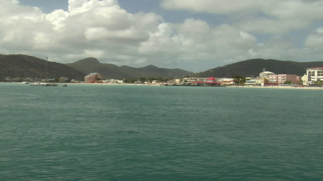 WS TS View coastal town, people swimming, and mountains in background/ Caribbean