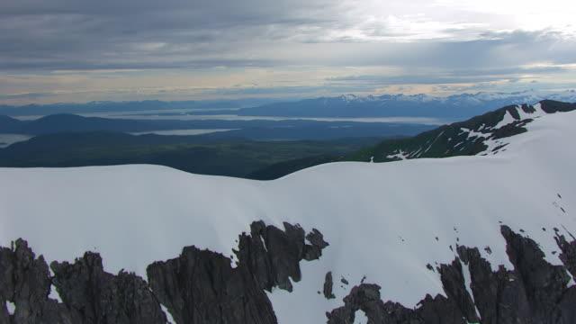 WS AERIAL View flying over mountain peaks to reveal Mendenhall Glacier terminus feeding into Mendenhall Lake / Alaska, United States
