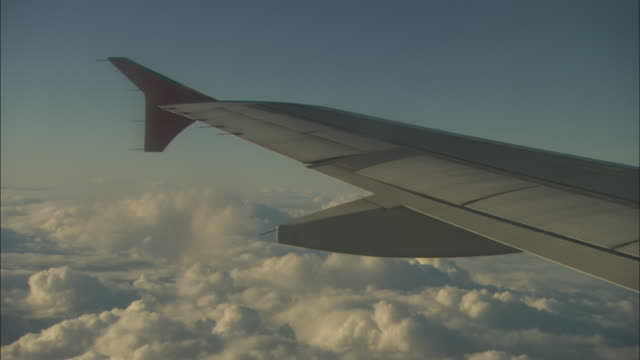 View from a window on a passenger aircraft as it flies above the clouds.