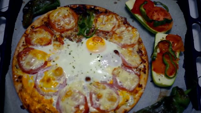 View from above of a vegetable pizza with egg and vegetables freshly baked