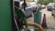 CU View from behind gas pump of long line of cars waiting for fuel at Trebol gas station / near San Cristobal, Tachira, Venezuela