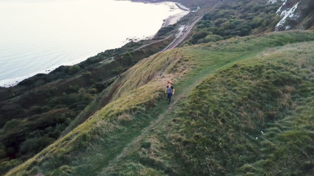 View from drone on young adult female running on cliff by sea