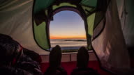View from inside a tent on the sea at sunset