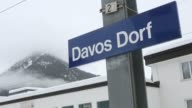 View from side of train tracks as train leaves Davos station passengers leaving platform / Davos Dorf station sign on platform Davos railway station...