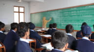 View from the back of the classroom of a female teacher writing on the blackboard for a class of middle school boys in uniform NO