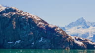 View from the side of a traveling cruise ship of snow covered rocky mountains along Glacier Bay