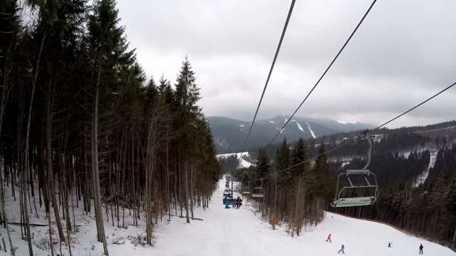 View from the ski lift. Ski lift and ski trail with skiers.