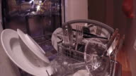 View from the sliding tray of dirty plates glasses and cutlery being put into a dishwasher