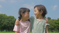 View of a boy and a girl with arm around smiling in summer at Seoulforest (the third largest park in Seoul city)