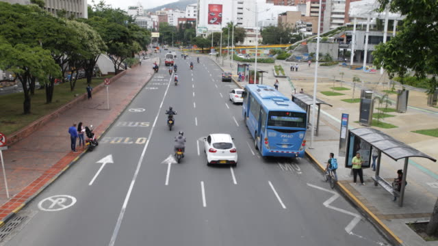 A view of a busy street shot from a pedestrian's bridge / camera tilt up showing an urban landscape
