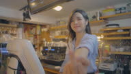View of a female barista showing obscene gesture in coffee shop