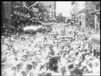 View of a radio tower / celebrating in the streets of Honolulu / civilians hold newspaper headlines noting the news of Japanese surrender / American...