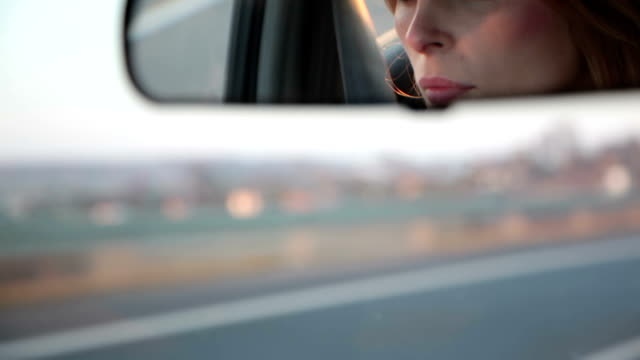 View of a woman in the car mirror