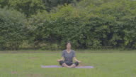 View of a woman meditating on yoga mat at a park