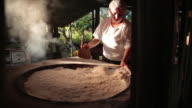 View of a woman processing manioc flour (three clips edited) - traveling movement