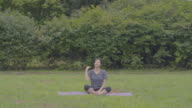 View of a woman stretching out on yoga mat at a park