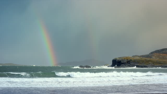 WS View of agitated waves breaking on beach and rocks with rainbow vanishing and clouds / Drumbeg, Scotland, United Kingdom