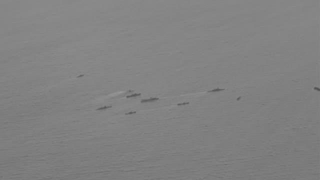 WS ZI TS HA View of Airplane flying over ocean looking down over battleships in ocean War