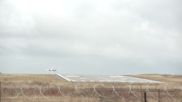 WS View of Airplane landing on runway (Shot over security fence) / Archangelsk, Archangelsk Oblast, Russia