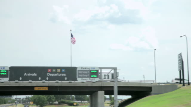 MS POV View of Airport signs and American flag from traveling car / Dulles, Virginia, United States
