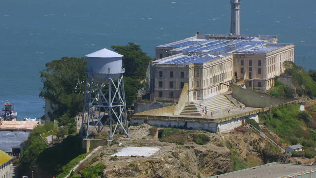 WS AERIAL POV View of Alcatraz Island at San Francisco Bay and modern city in background / San Francisco, California, United States