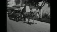 View of Algiers from boat in harbor Vichy France troop transport 'Sidi Bel Abbes' anchored at dock / two horses pulling bus down street / view of...