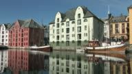 WS PAN View of ancient sailing ship next to houses / Alesund, Norway