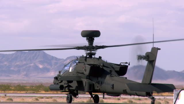 MS PAN View of Apache military attack helicopter with spins around to roll towards runway near desert / Los Angeles, California, USA