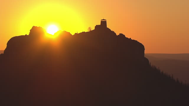 WS AERIAL TS View of approaching Harney Peak Fire Tower with bright sun on horizon and Fire Tower dark / South Dakota, United States