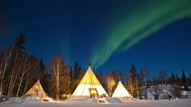 WS T/L View of Aurora above snow covering forest and teepees / Yellowknife, Northwest Territories, Canada