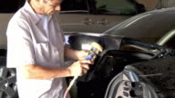 MS ZI View of auto body mechanic spraying sanding power tool across trunk lid of car / Cathedral City, California, USA