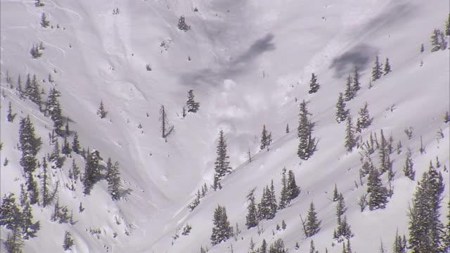 WS PAN TD View of avalanche exploding through snowy ridge / Bozeman, Montana, USA