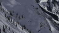 WS TD PAN View of avalanche exploding through snowy ridge / Revelstoke, British Columbia, Canada