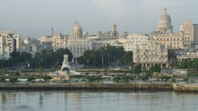 WS View of Batista palace near sea and running vehicles on road / Havana, Cuba